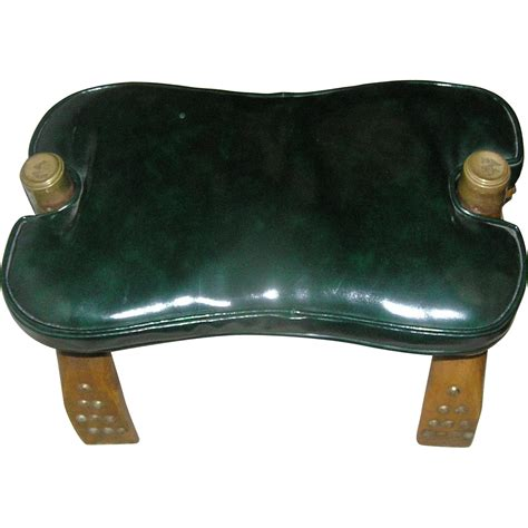 camel back stool with a leather like cushion of