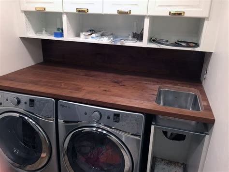 utility sink with cabinet and countertop a walnut counter and backsplash in the laundry room