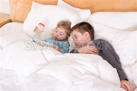 brother sister share bed happy little brother and sister lying in bed stockraphy