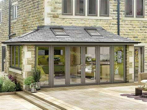 modern grey conservatory attached to a stone house with wood decking in front of it things i