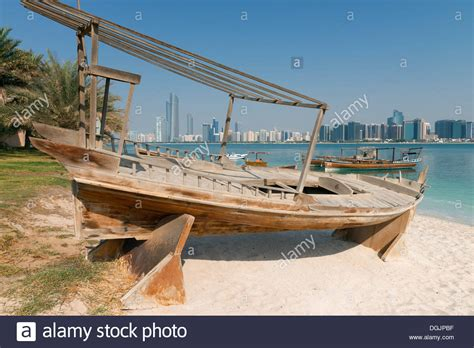 old boat uae skyline of modern abu dhabi and old traditional fishing
