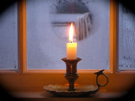 window on a burning books winter solstice candle in the window looking through