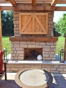 Farmhouse outdoor fireplace with custom cedar tv cabinet farmhouse