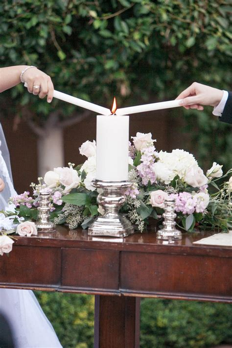 groom light unity candle during outdoor ceremony floral arrangement sits on table