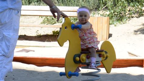 lady swinging baby woman swing baby girl in field on rocking horse stock