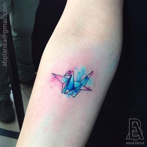 crane tattoo forearm of an origami crane with a watercolor