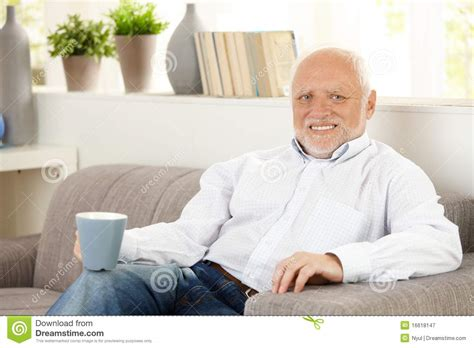 having on the sofa smiling elderly man having coffee on sofa royalty free