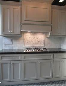 light gray backsplash gray cabinets black counters slate herringbone floor