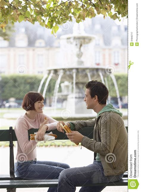 eating bench smiling couple eating baguette on park bench royalty free