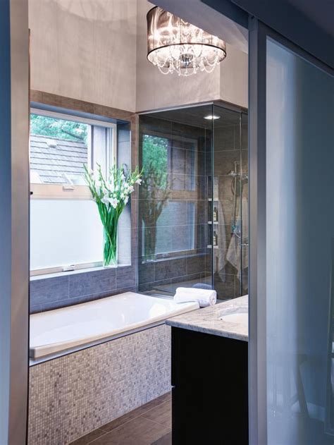 modern gray bathroom with tiled bathtub and glass enclosed