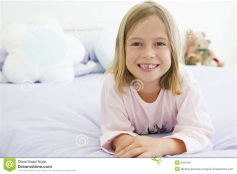 girls in bed young girl lying on her bed in her pajamas stock image