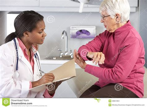doctor examining woman doctor examining female patient with elbow pain stock