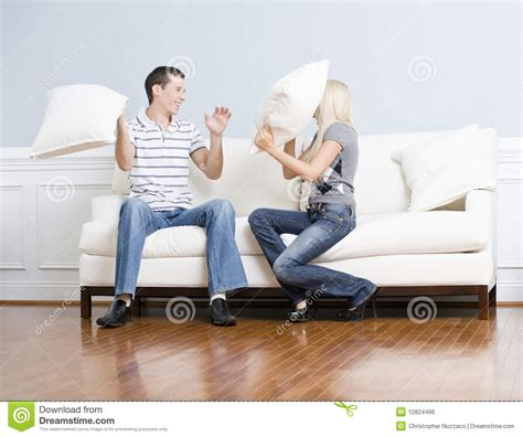 having on the couch young couple having a pillow fight on sofa royalty free