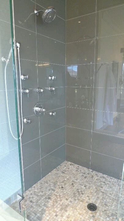bathroom stall walls large grey glass tiles on wall smaller mosaic stone like