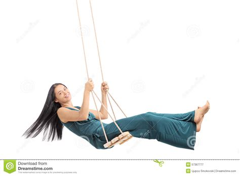 women and swinging fashionable woman swinging on a wooden swing stock photo