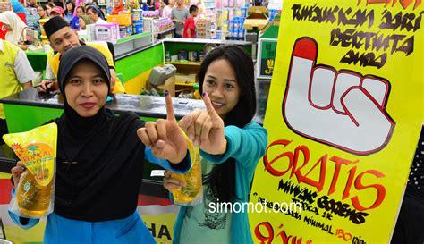 Minyak Goreng Di Surabaya dua pengunjung menunjukkan tinta yang ada di jari usai