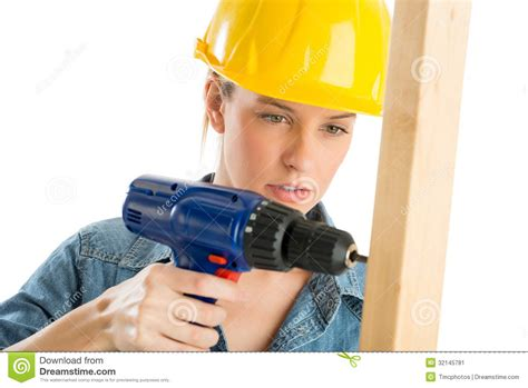 using an construction worker using cordless drill on wooden plank