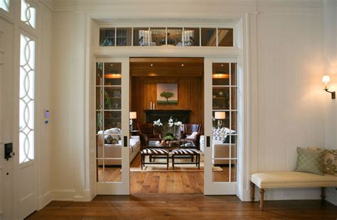 sliding french doors living room with green sofa and glass pocket doors transitional entrance foyer