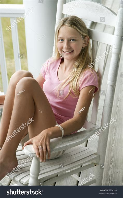 Caucasian pre teen girl sitting in rocking chair on porch smiling stock photo 2724289