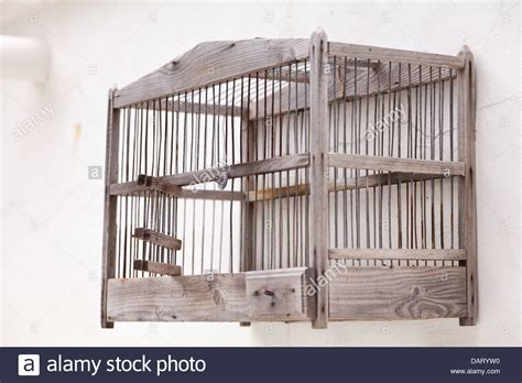 old wooden bird cage hanging empty on a whitewashed wall stock photo 58304428 alamy