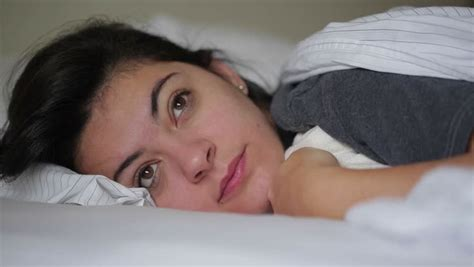 lying down in bed girl rubbing her eyes laying down in bed then closing her eyes stock footage video