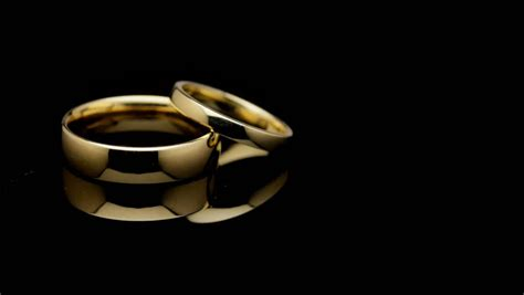 stock clip of pair of wedding rings turning on black