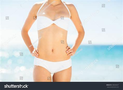 bikini wax after c section mid section of woman in white bikini posing on beach stock