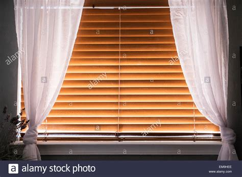 wooden blinds with curtains a window covered with closed wooden window blinds with