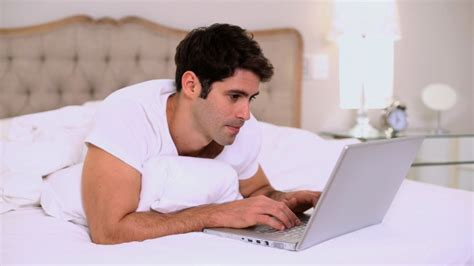 laptop in bed smiling handsome man using laptop in bed by lightwavemedia videohive