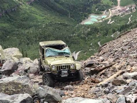 wrecked black jeep grand photo shows damaged jeep hanging on cliffside on black