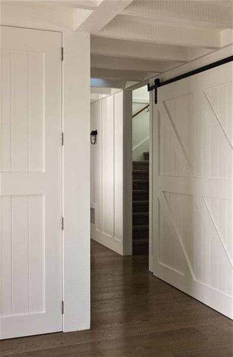 farmhouse hallway white barn doors  dark wood floors