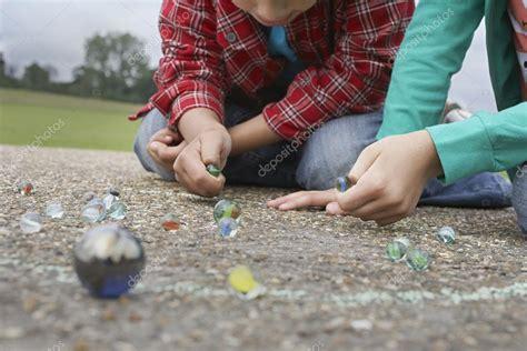 imagenes niños jugando a las canicas ni 241 o y ni 241 a jugando a las canicas fotos de stock