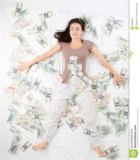 Female Bedroom Ideas happy woman sleeping in a bed full of money stock image