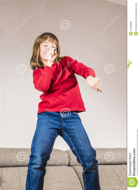 standing on the couch little girl singing stock photo image 51623538