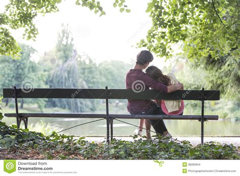 couple sitting on bench rear view of romantic young couple sitting on bench at