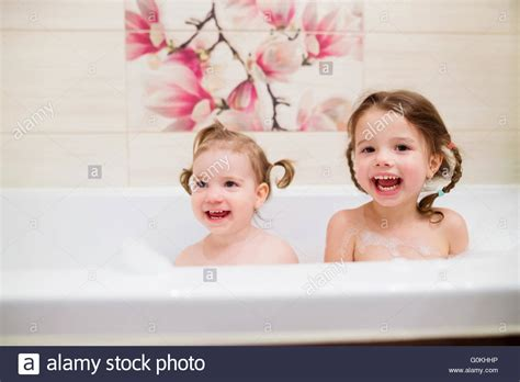 two girls in a bathtub two little girls having bath with bubbles in bathtub stock