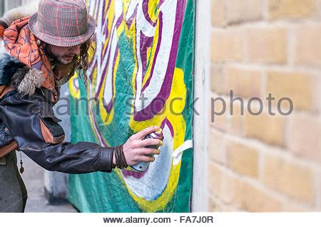spray painter croydon graffiti artist with spray can painting a troll onto