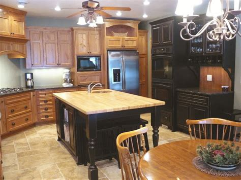 rustic cherry cabinets with black island kitchen