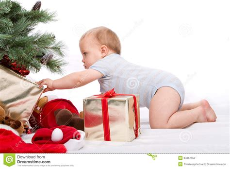 santa baby boy reaching for christmas gift stock photo