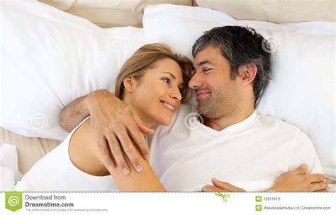 couples in bed affectionate couple hugging lying in bed stock photos