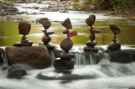 artist creates serene art by balancing rocks lost in