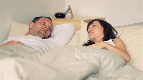 wife in bed wife and husband tv remote control conflict in bed stock