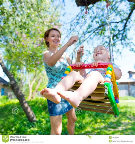 moms swing happy mother rocking a laughing baby on a swing stock