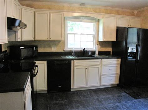 antique white kitchen cabinets with black appliances