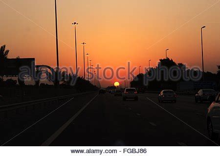 car silhouette and sun at sunset on highway, usa stock