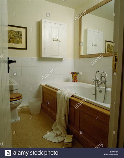 White Bathroom Carpet by Large Mirror Above Panelled Bath In White Bathroom With