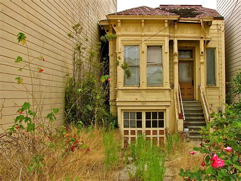 garden between houses an abandoned home in san francisco sandwiched between two modern apartment buildings on a
