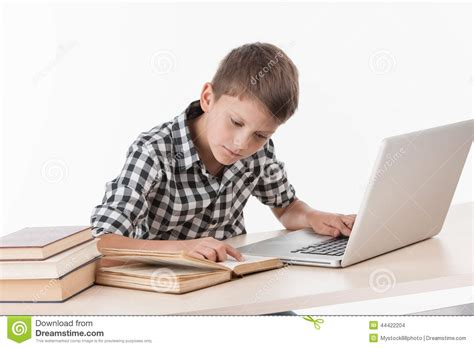 what desk is using happy boy using laptop at table stock photo