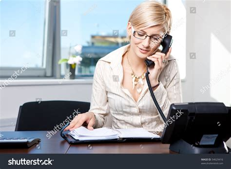 on the office desk businesswoman sitting at desk in office talking on