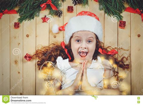 praying  girl   festive garland  wooden background stock photo image